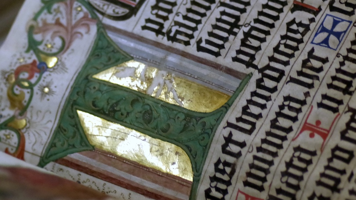 Close-up of an illuminated medieval manuscript. Calligraphy and gilt capital letter.