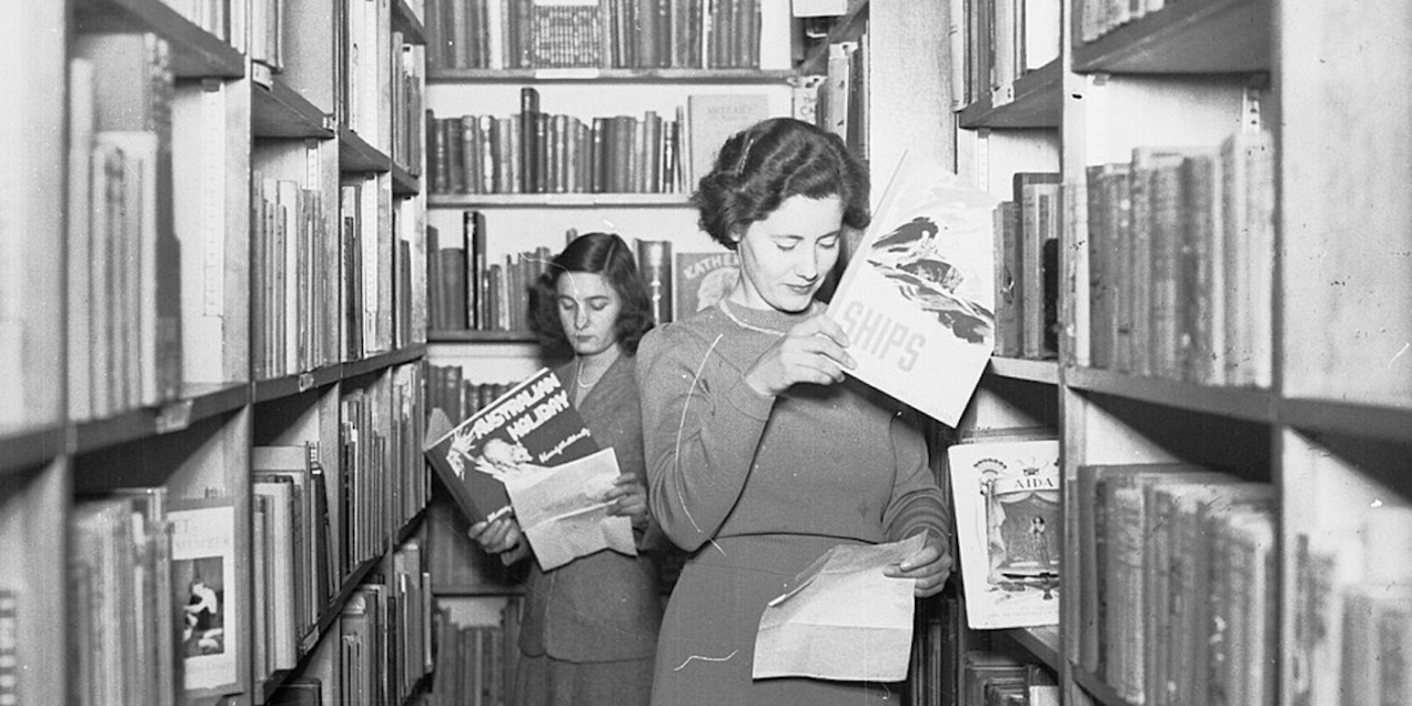 """Two women browsing books on """"Australian History"""" and """"Ships"""" in the library stacks in the 1940s."""